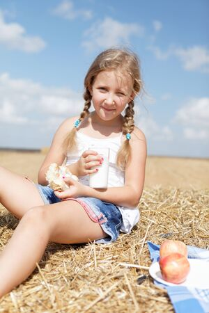 stubble field: cute girl eating healthy meal summer Stock Photo