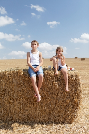 brother and sister in the hay in the countryside photo