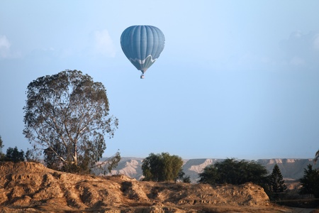 balloon flying against a rocky landscape photo