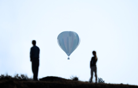people are looking at a balloon flying away in the distance photo