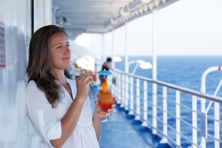 cute girl with a cocktail on a journey to the sea