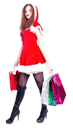 pretty long-legged girl dressed as Santa with shopping on an isolated photo