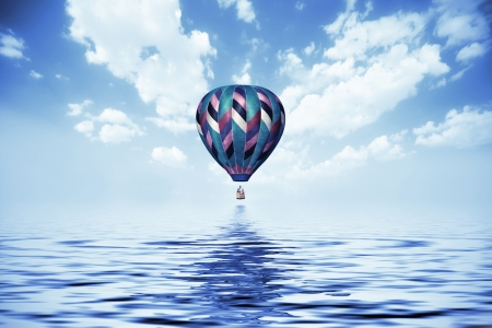 balloon flying low over the water Stock Photo