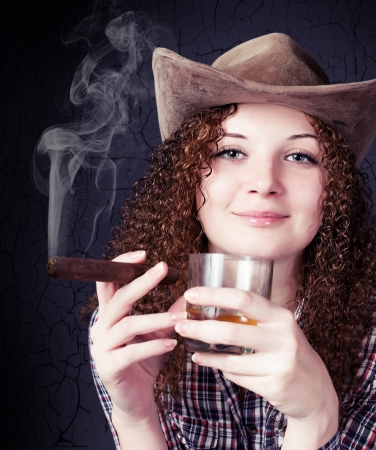 pretty curly girl in a cowboy hat with a cigar photo