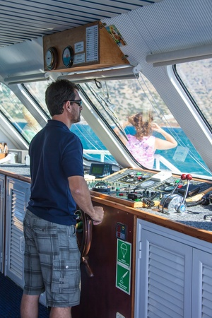 SANTORINI  GREECE - 4 JULY 2012: skipper, in the workplace, steers the ship 4 july 2012 Santorini.