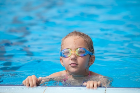 Girl swims in the pool, summer day photo