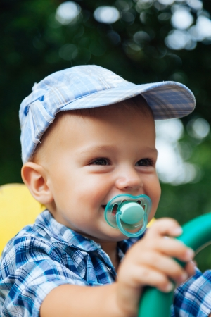 Portrait of a laughing baby with pacifier outside in the summer Stock Photo