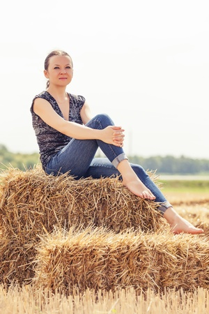 pretty girl sitting on a haystack on the summer day photo