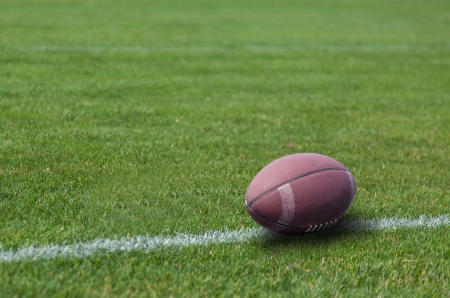American rugby ball on the grass in the stadium Stock Photo