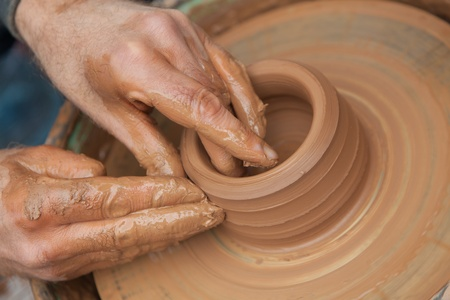 craftsman works in clay pot outside photo