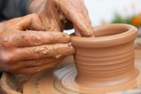 craftsman works in clay dishes outside
