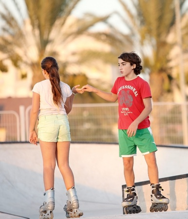 boy helps her friend in the park, roller skating