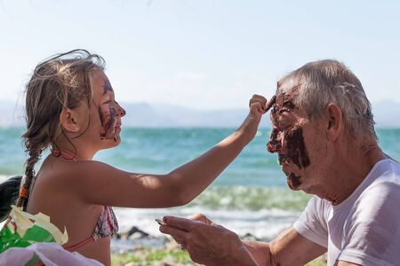 smears: granddaughter grandfather smears face with mud summer day