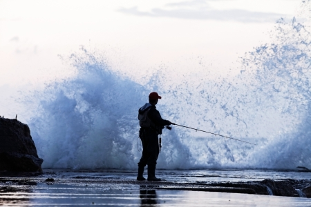 man fishing in extreme storm, dangerously