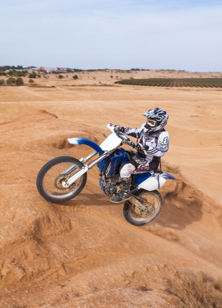 racer on a motorcycle up the hill in the desert in summer