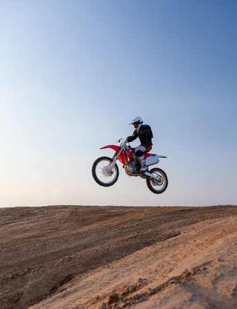 rider performs stunts on a motorcycle in the desert Stock Photo