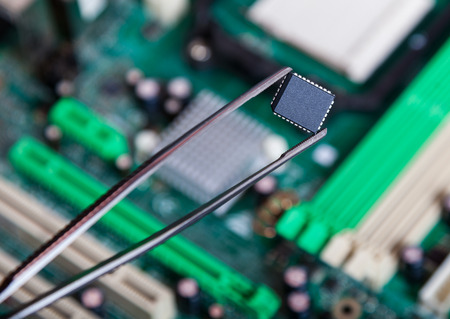electronic background: computer chip with tweezers, electronic background