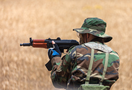 man with an AK holding at gunpoint, the military conflict photo
