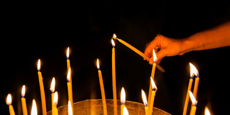 sepulchre: man lights a candle in the church of the Holy Sepulchre in Jerusalem