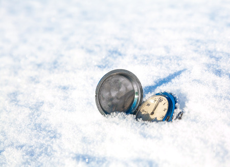 antique clock lay on a snowy background photo