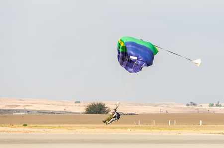 parachutists: parachutists a touchdown on the background of the desert