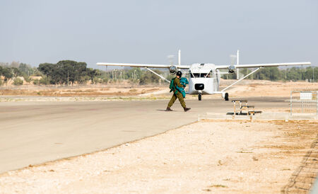 airplane ultralight: a man in a parachute outfit passes by aircraft