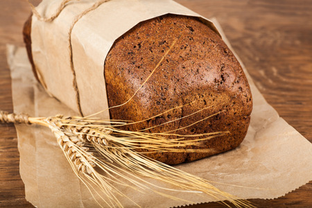 bread with ears of wheat on wooden background photo
