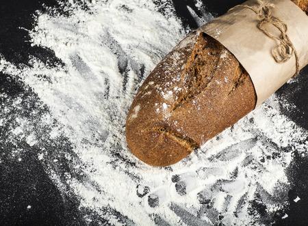 long loaf: black long loaf on a dark background with flour