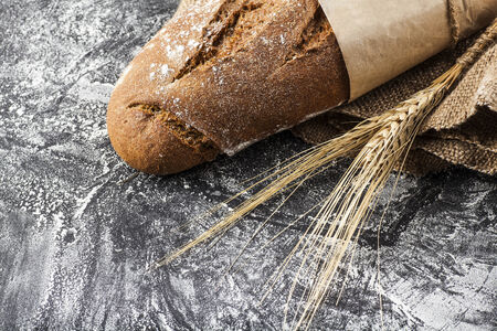 long loaf: long loaf with ears of wheat on a dark background with flour