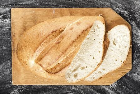 long loaf: sliced white long loaf on a dark background with flour