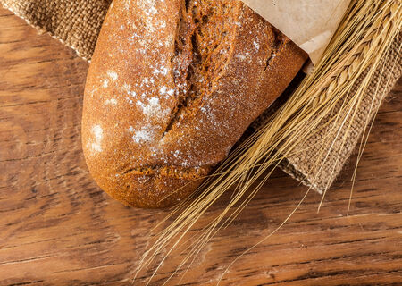 bread and ears of wheat on the wooden background photo