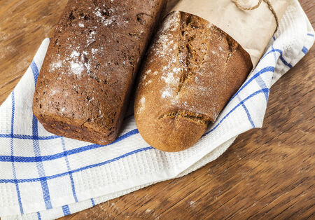 two loaves of bread on a wooden background photo