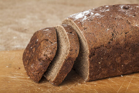 sliced loaf of black bread on a wooden board photo
