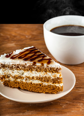 porcion de torta: piece cake on a plate and black coffee on a wooden background Foto de archivo