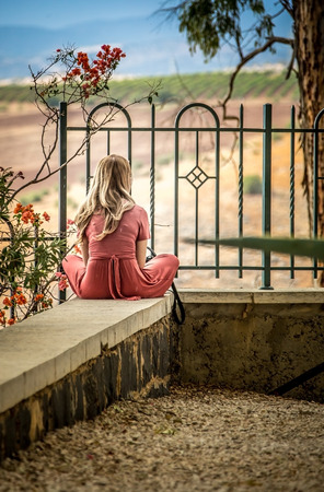 holyland: blonde girl in a pink dress sitting back