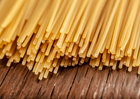 posted: spaghetti posted on the a row on a wooden background