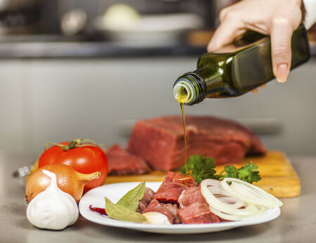 pours: Chef pours olive oil on meat fillet
