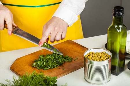 shred: cook woman finely shred dill and parsley close-up