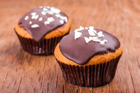 chocolate icing: two cupcakes in chocolate icing on a wooden background
