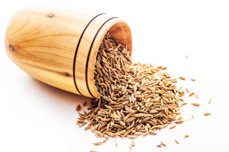 cumin: spice cumin in a wooden bowl on a white background Stock Photo