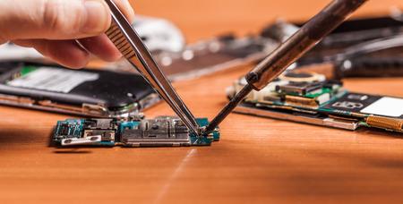 auf einem hölzernen Hintergrund Arbeitnehmer die Reparatur gebrochen Telefon