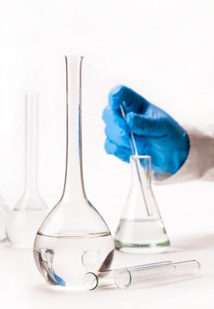 laboratorian: mix reagents into the flask on a white background Stock Photo