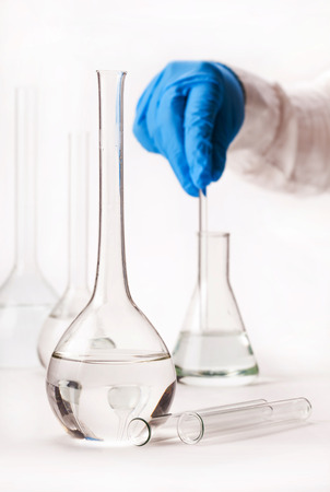assistant mix reagents into the flask on a white background Stock Photo