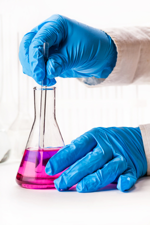 reagents: mix reagents into the flask on a white background Stock Photo