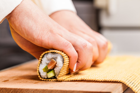 cook turns nori sheet with filling in the roll closeup