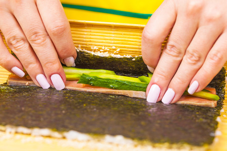 filling in: cook turns nori sheet with filling in the roll Stock Photo