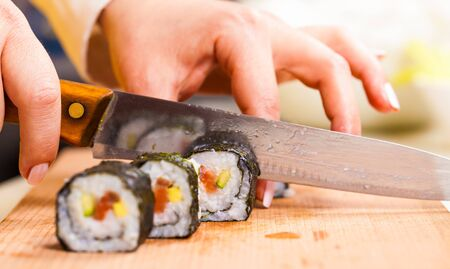 japanese cooking: hand cuts the roll closeup on a wooden board