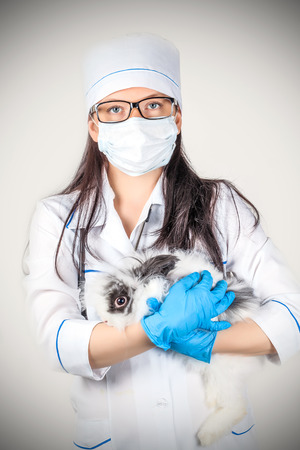 portrait of a doctor with a decorative rabbit in hands photo