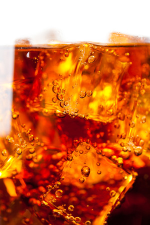 carbonation: Cola with ice cubes and bubbles closeup