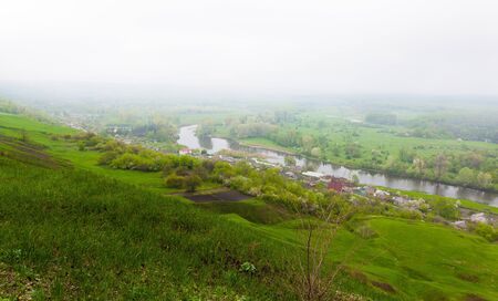 foggy hill: village and river landscape view from hill in foggy weather